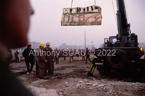 East Berlin, East Germany<br /> November 12, 1989<br /> <br /> East and West Germans watch as the first section of the Berlin Wall is removed by a crane at Potsdamer Platz. Germans gathered as the wall is dismantled and the East German government lifted travel and emigration restrictions to the West on November 9, 1989.