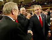 United States President. George W. Bush shakes hands with Defense Secretary Donald Rumsfeld as Secretary of State Colin Powell looks on as the President makes his way into the House Chamber for his State of the Union address January 20, 2004.  Bush addressed the Joint Session of Congress delivering his address.  <br /> Credit: Kevin Lamarque / Pool via CNP