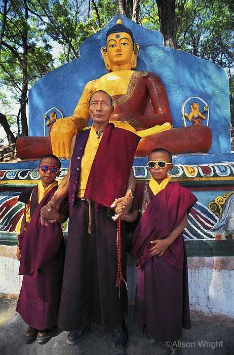 Tibetan Lama and his twin grandsons at Swayambunath, Kathmandu, Nepal.<br /> Lobsang Thenba, a Tibetan lama living in exile, stands proudly with his two young grandsons at Swayambunath stupa in Kathmandu, Nepal. These twins have been trained to be monks since birth, and one has recently been recognized as a being reincarnated as a high lama or Rinpoche.