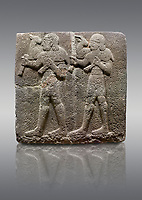Picture &amp; image of Hittite monumental relief sculpted orthostat stone panel of a Procession Basalt, Karkamıs, (Kargamıs), Carchemish (Karkemish), 900-700 B.C.  Anatolian Civilisations Museum, Ankara, Turkey. Young male servants of Kubaba while carrying sacrificial animals on their shoulders. <br /> <br /> Against a gray background.