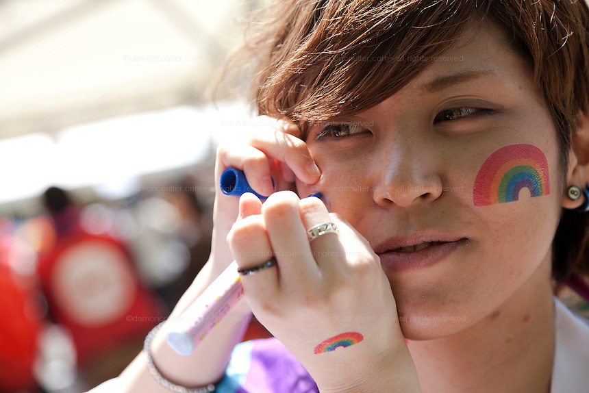 A woman has her faces painted with a rainbow at Tokyo Rainbow Pride festival, Yoyogi Park, Tokyo, Japan. Sunday April 27th 2014 This was the third year this annual gay-pride event has been held in Japan capital.with food, fashion and health care stalls and musical performances set up in Yoyogi Park event square and a colourful parade around Shibuya at 1pm.