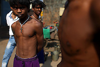 Bare chested young men stand in the street in Kolkata.<br /> <br /> To license this image, please contact the National Geographic Creative Collection:<br /> <br /> Image ID: 1925757 <br />  <br /> Email: natgeocreative@ngs.org<br /> <br /> Telephone: 202 857 7537 / Toll Free 800 434 2244<br /> <br /> National Geographic Creative<br /> 1145 17th St NW, Washington DC 20036