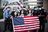 NEW YORK, NY - MAY 7: A group of medical workers in front of Langone Health Hospital in New York hold a U.S. flag. as three JetBlue planes pay tribute to healthcare workers with a special low-altitude flight over Manhattan during the COVID-19 pandemic on May 7. 2020 in New York, NY. COVID-19 has spread to most countries in the world, claiming more than 270,000 lives and more than 3.9 million people have been infected. (Photo by Andres Mesa / VIEWpress via Getty Images)