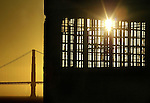 The setting sun beams through a maze of prison bars on the west end of the island with the Golden Gate Bridge in the background. A group of photographers from the Media Alliance overnighted on Alcatraz and documented their tour  in San Francisco California.