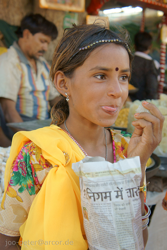 girl eating snack on her visit of  camel fair in Pushkar, Rajastan, India