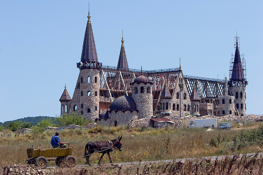 Ravadinovo, Bulgaria..A donkey and cart pass by an as-yet unnamed hotel resort which has been in the process of construction for the last eight years near the coastal town of Sozopol. Rapid overdevelopment of the Back Sea coast has led to widespread environmental destruction, and many properties lie uncompleted or empty.