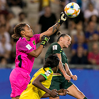 GRENOBLE, FRANCE - JUNE 18: Nicole Mcclure #13 of the Jamaican National Team punches ball clear of Chloe Logarzo #6 of the Australian National Team during a game between Jamaica and Australia at Stade des Alpes on June 18, 2019 in Grenoble, France.