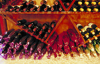 Stacked wine bottles in display case showing corked ends with variety of wine colors at a winery in Geyserville, CA. California.