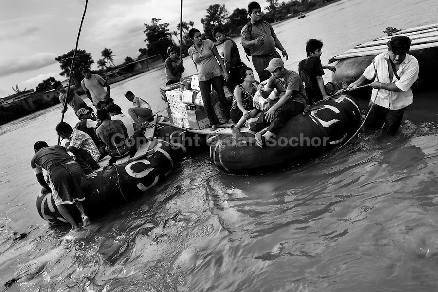 Makeshift inner tube rafts, carrying smuggled goods, border area workers and immigrants from Central America, cross the Suchiate river in Tecún Umán, Guatemala, 22 May 2011. Having no migration or commercial controls, the Suchiate river serves as an illegal crossing point between the southern Mexican state of Chiapas and Guatemala. Every day, hundreds of people from both countries, crossing the river on the unstable rafts called ?camaras?, smuggle soft drinks, toilet papers, fruits, vegetables and other supplies. The river crossing is also widely used by the Central America immigrants heading to the north, to the United States, in the search of better life.