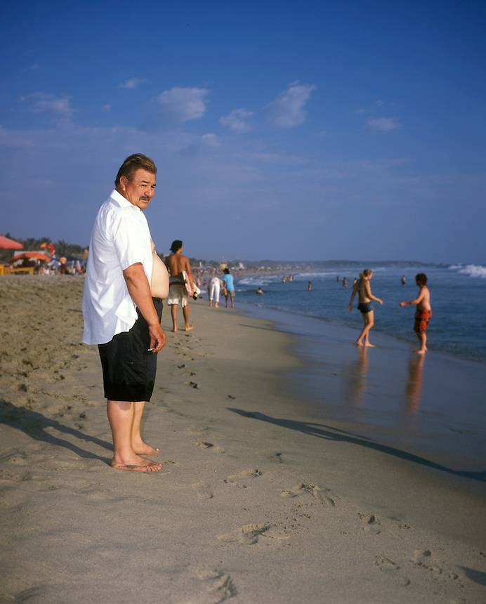 A man smokes a cigarette by the edge of the sea. Puerto Escondido during spring break (semana santa) vacation 2006