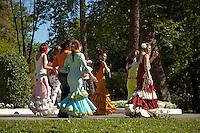 Women in flamenco dress walking through Maria Luisa Park towards the Seville Spring Fair, Seville, Andalusia, Spain.