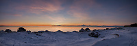 The setting sun paints wondrous colors on Mount Redoubt, Mount Iliamna and Cook Inlet during a winter scene on Kenai Beach in south central Alaska.