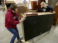 Anna Jeldorks (left) and Anna (cq) Slade, both volunteers and members of the Church of Jesus Christ and Latter Day Saints, move move recently donated office furniture Tuesday, February 11, 2020, at the Habitat for Humanity ReStore of Washington County in Fayetteville. The store, that is open Tuesday through Saturday. Check out nwaonline.com/200212Daily/ and nwadg.com/photos for a photo gallery.<br /> (NWA Democrat-Gazette/David Gottschalk)