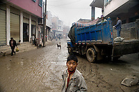 "A boy stands in the muddy streets of Sheng Cun, in Yuanyang County, Yunnan Province, China, while workers unload a truck full of concrete to be used to improve roads in the area.  ""Sheng Cun"" is translated as ""Successful Village"" in local tourist brochures."