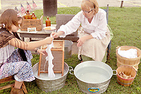 """RACHEL DICKERSON/MCDONALD COUNTY PRESS Linda Patterson, right, and her granddaughter, Eliza Ruby, demonstrate pioneer laundry during """"History Live"""" at the McDonald County Museum re-opening on Saturday, May 25."""