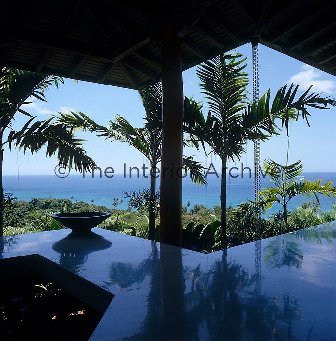 The palm trees are reflected in the polished floor of the walkway that joins the bedrooms to the main living area