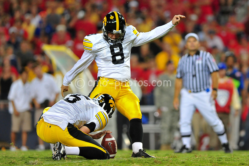 Sept 18, 2010; Tucson, AZ, USA; Iowa Hawkeyes kicker Trent Mossbrucker (8) kicks an extra point out of the hold of Iowa Hawkeyes punter Ryan Donahue (5) in the 4th quarter of a game against the Arizona Wildcats at Arizona Stadium.  Arizona won the game 34-27.