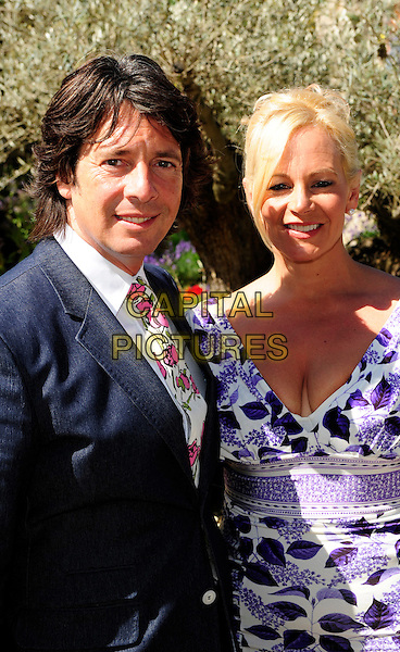 LAURENCE & JACKIE LLEWELYN-BOWEN .The Chelsea Flower Show - Press & VIP Day at Royal Hospital Chelsea. .London, England, UK, 24th May 2010..half pink roses length  married couple husband wife navy blue suit tie white and purple print dress floral .CAP/CJ.©Chris Joseph/Capital Pictures.