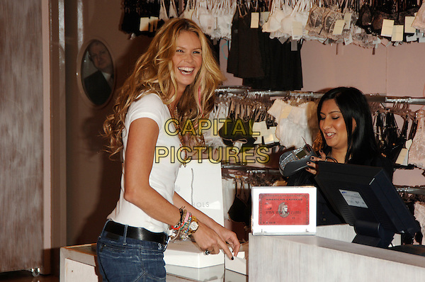 ELLE MacPHERSON.Photocall to launch the new American Express Red credit card - which donates 1% ofevery transactionto the Global Fund to help women and children affected by AIDS/ HIV in Africa, Harvey Nichols, London, England, March 1st 2006..half length jeans white t-shirt t shirt bracelets watch necklace jewellery shopping buying purchase.Ref: PL.www.capitalpictures.com.sales@capitalpictures.com.©Phil Loftus/Capital Pictures