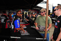 Mar. 10, 2012; Gainesville, FL, USA; NHRA top fuel dragster driver Antron Brrown (left) signs autographs and greets fans during qualifying for the Gatornationals at Auto Plus Raceway at Gainesville. Mandatory Credit: Mark J. Rebilas-