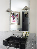 A guest bathroom is fitted in Carrara marble with sconces by Nicholas Haslam