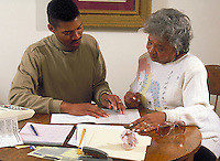 African-american son helping mother with paperwork