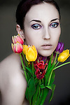 Young girl with combed back dark hair and colourful make up and pale skin , holding a bunch of tulips with simple background.