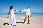 Asian bride and groom stroll while holding hands on Lanikai beach as the couple celebrates their honeymoon.