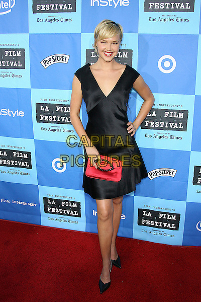 """ARIELLE KEBBEL.2006 Los Angeles Film Festival Opening Night - """"The Devil Wears Prada"""" Premiere held at the Mann Village Theater, Westwood, California, USA..June 23rd, 2006.Photo: Zach Lipp/AdMedia/Capital Pictures.Ref: ZL/ADM.full length black dress satin pink clutch purse.www.capitalpictures.com.sales@capitalpictures.com.© Capital Pictures."""