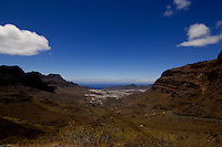 San Nicholas in the background against the blue sky and Atlantic of the rugged Canarian mountain pass on the west coat of Gran Canaria, Mogan to Agaete road. Gran Canaria, Canary Islands, Spain.