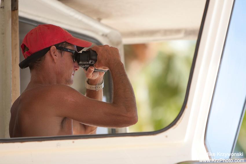 Caucasian lifeguard looking through binoculars in Waikiki, Honolulu, Oahu, Hawaii