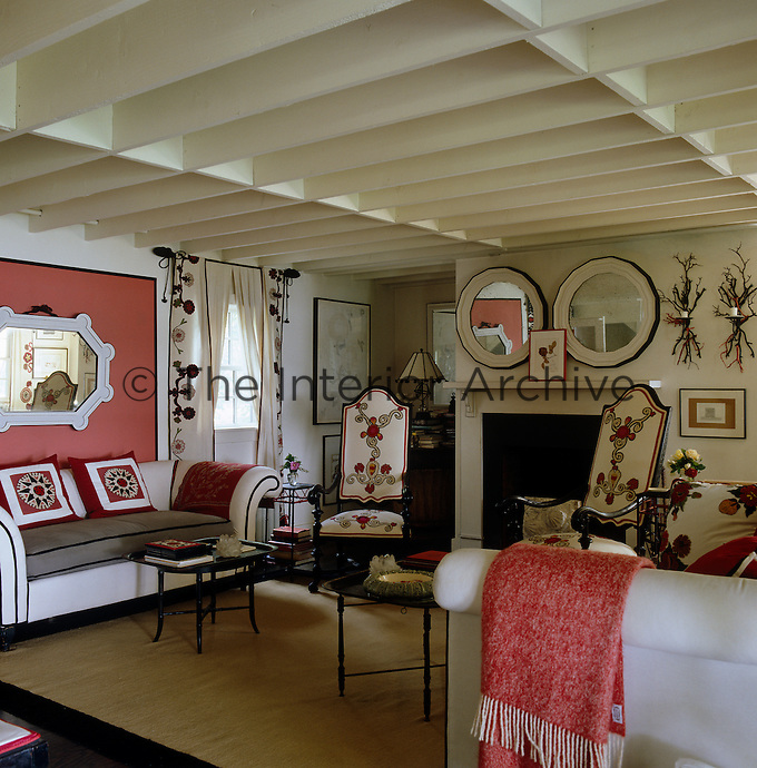 The red, white and black colour scheme of this living room is reflected in the intricate detailing of the chairs, cushions and curtains