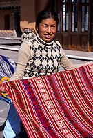 Peru, Yucay.  Quechua Girl and fabric.