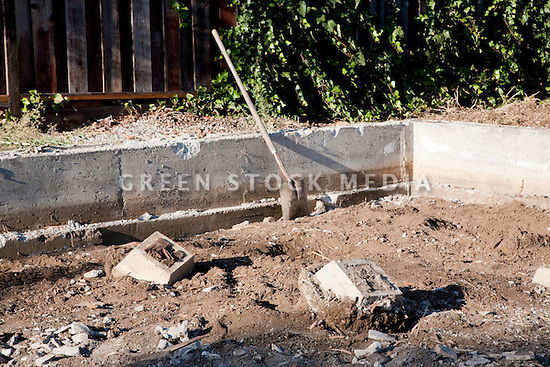 A shovel leaning on a concrete border of a house foundation which remains after demolition of a single family home on a 10,000 square foot lot. The site will have a 4,060 square foot two story single family home with an in-law unit. Cupertino, California, USA