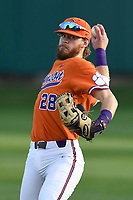 Right fielder Seth Beer (28) of the Clemson Tigers warms up between innings of a game against the William and Mary Tribe on February 16, 2018, at Doug Kingsmore Stadium in Clemson, South Carolina. Clemson won, 5-4 in 10 innings. (Tom Priddy/Four Seam Images)