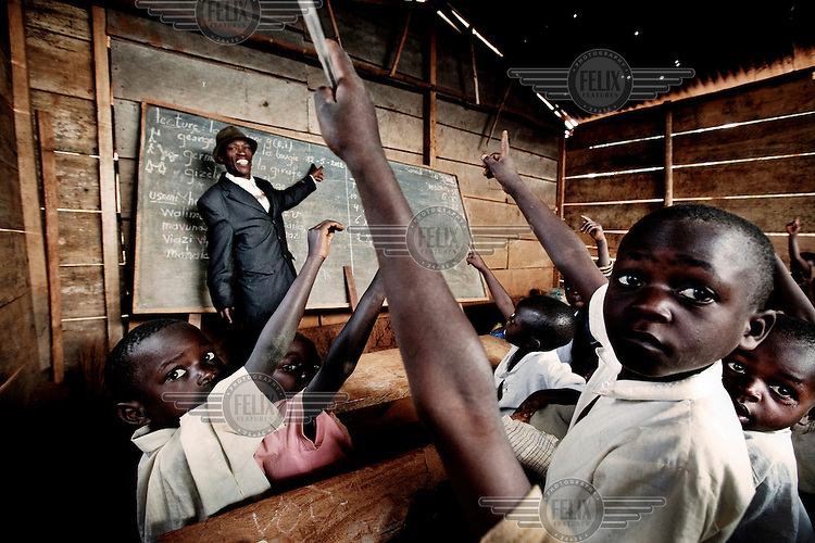 Valere, a teacher at the Janvier Kakule school, stands at the class blackboard with a room of students many of whom come from families who had fled from the war in eastern Congo.