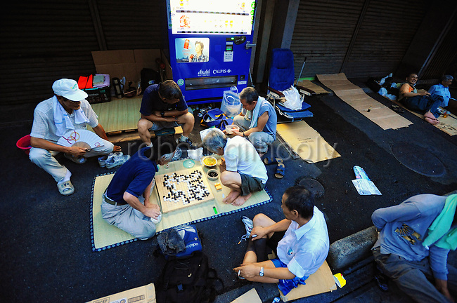 Unemployed men play games and drink  outside the Nishinari Labor Welfare Center in the Kamagasaki district of Osaka, Japan. Many of the men are homeless and although there are shelters in the area prefer to sleep rough and be first in line for the day labor jobs that are handed out through the welfare center each day.