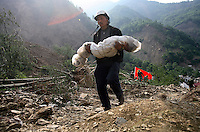 A man carries the body of his son, a third grader, that he recovered from the ruins of a collapsed school complex in Beichuan, Sichuan, China on 15 May 2008. China now estimates the death toll to be around 50,000 as prospects of survival for those still buried diminishes.