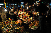 Old woman selling dried-flower arrangements and potted plants from roadside stall, at night. Da Lat, Vietnam