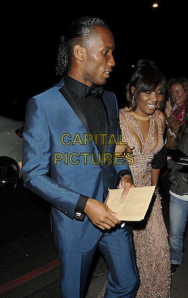 Didier Drogba & Alla Drogba.Attending the Didier Drogba Foundation Charity Ball, Dorchester Hotel, Park Lane, London, England, UK, .10th March 2012..half length blue suit black shirt  bow tie  beige beaded dress  married husband wife .CAP/CAN.©Can Nguyen/Capital Pictures.