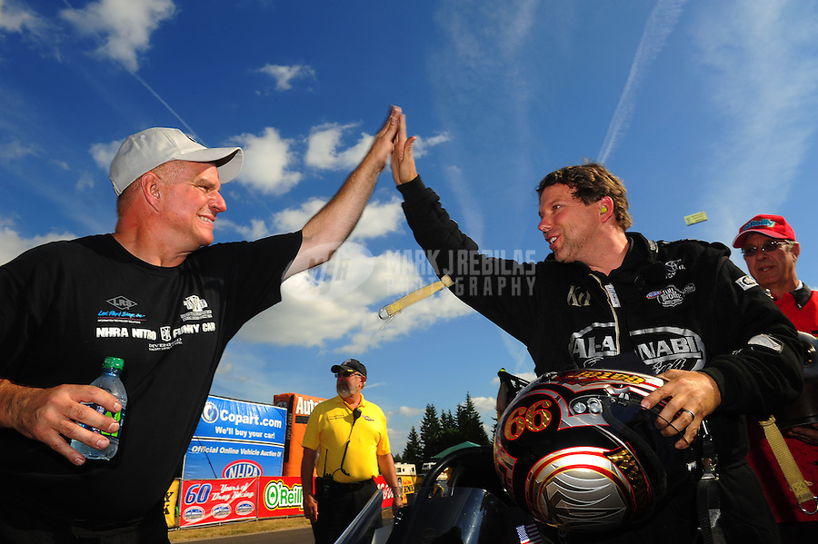 Aug. 7, 2011; Kent, WA, USA; NHRA top fuel dragster driver Del Worsham (right) is congratulated by funny car winner Tim Wilkerson after winning the Northwest Nationals at Pacific Raceways. Mandatory Credit: Mark J. Rebilas-