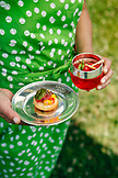 USA, Tennessee, Nashville, Iroquois Steeplechase, woman holding Moonshine Cherry-Basil Blush and and the Beef Tenderloin sandwich on a single serve plate