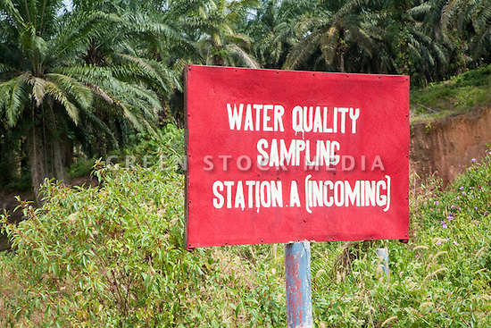 A water quality sampling station sign in a riparian section on a palm oil plantation. The Sindora Palm Oil Plantation, owned by Kulim, is green certified by the Roundtable on Sustainable Palm Oil (RSPO) for its environmental, economic, and socially sustainable practices. Johor Bahru, Malaysia