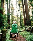 USA, California, Eureka, senior woman sitting in redwood forest