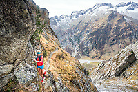 A female trail runner on a steep, exposed trail, using cables for security. Salbit, Switzerland.