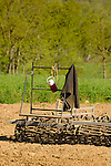 Harrowing farm implement in field with Amish jacket and thermos.