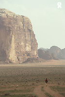 Jordan, Aqaba, Wadi Rum, woman hiking on desert track, rear view (Licence this image exclusively with Getty: http://www.gettyimages.com/detail/200387978-001 )