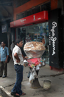 A modern Gulgappe seller in front of a Pepe Jeans showroom in Kolkata.  Street food stalls are serving the office goers for decades. All kind of Indian foods are available on the street at an affordable price. They sale them openly. Street food stalls are another results of unempoloyment and over poppulation. They serve millions of people in India. Kolkata, West Bengal,  India  7/18/2007.  Arindam Mukherjee/Landov