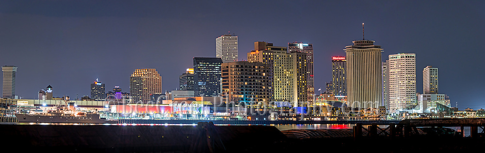New Orleans skyline pano after dark with the high rise buildings along the waterfront and the lights on in the downtown skyscrapers make a nice image of the city.