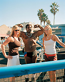 USA, California, Los Angeles, a bodybuilder strikes a pose with a couple of California Girls at Muscle Beach, Venice Beach